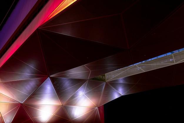 Architektura nowoczesna. pomarańczowo-czerwona geometryczna metaliczna konstrukcja z trójkątnych części. streszczenie tło w ciemności.