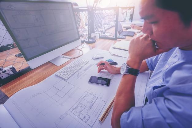 Architektura pracuje kreślący na architektonicznym projekcie przy budową przy biurkiem w biurze