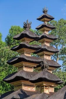 Architektura świątyni hinduskiej na wyspie bali w ubud, indonezja, azja. wysoka wieża z dachem krytym strzechą i błękitne niebo