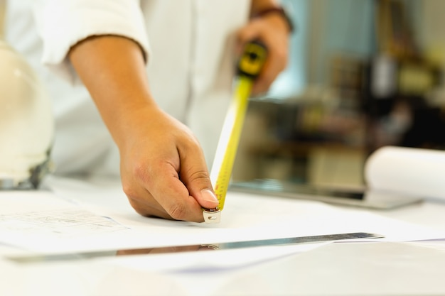 Architektury ręki pomiarowy projekt z taśmy masurem na pracującym stole.