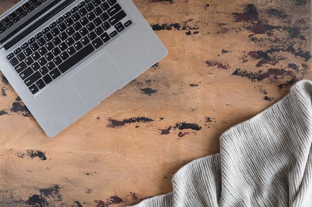 Archiwalne biurko drewniane biurko z laptopem i szary dzianinowy koc. widok z góry i układ płaski z miejscem na kopię,