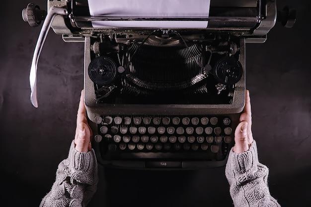 Archiwalne narzędzie dziennikarskie. maszyna do pisania retro. pisarz jest w pracy. pieczęć powieści. koncepcja pisarz dziennikarz.