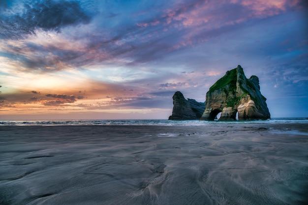 Archway islands, dramatyczne formacje skalne pod kolorowym niebem na wharariki beach nelson