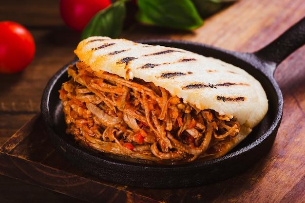 Arepa świeżo przyrządzona z rozdrobnionym mięsem