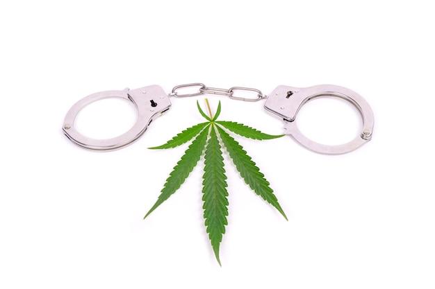 Aresztowanie za medyczną marihuanę, handel narkotykami z konopi, kajdanki i zielony liść.