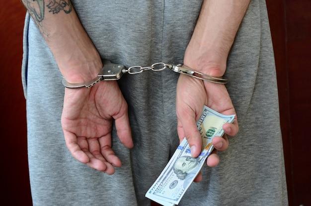 Aresztowany facet w szarych spodniach z kajdankami trzyma dużą ilość banknotów dolarowych. widok z tyłu