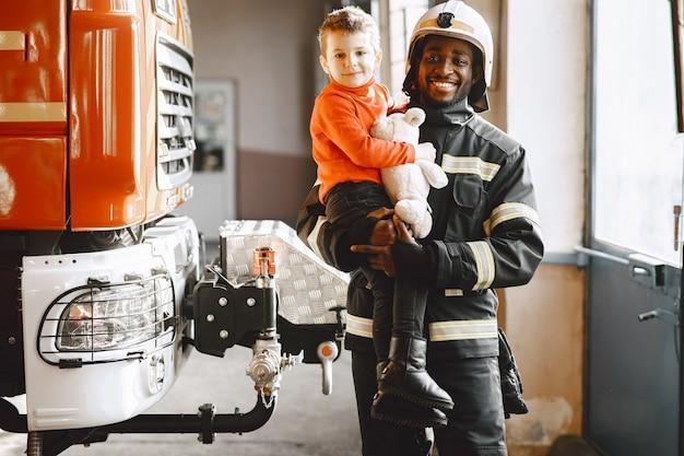 Arfican strażak w mundurze. człowiek przygotowuje się do pracy. facet z dzieckiem.