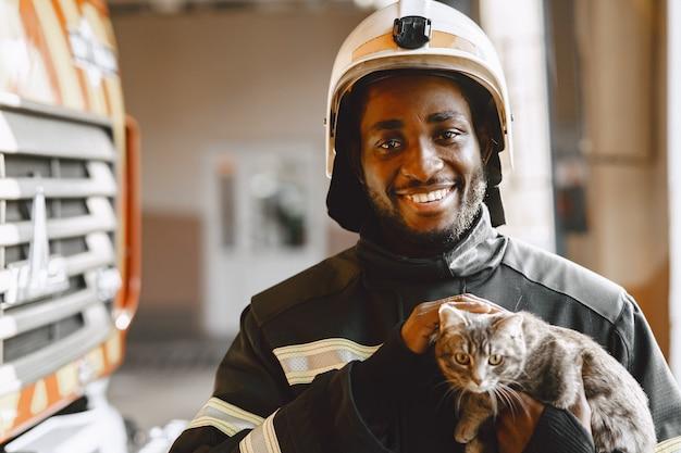 Arfican strażak w mundurze. człowiek przygotowuje się do pracy. facet z kotkiem.