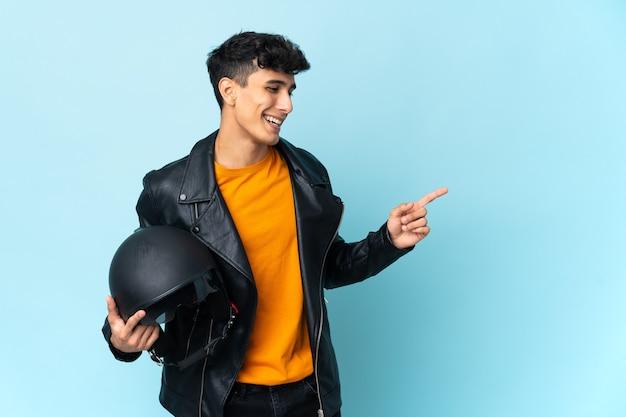 Argentyńczyk w kasku motocyklowym wskazuje palcem w bok i prezentuje produkt