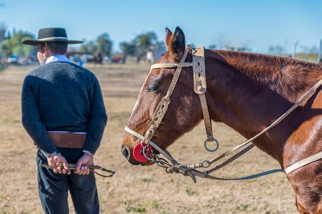Argentyński gaucho obok swojego konia na pierwszym planie.