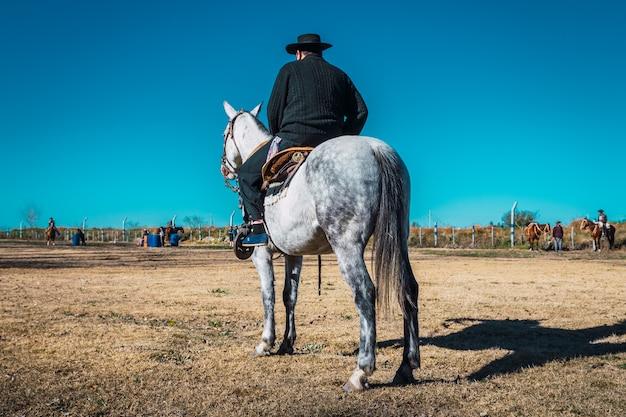 Argentyński gaucho z kapeluszem na koniu