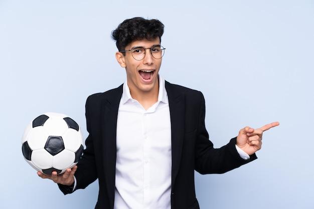 Argentyński trener piłki nożnej na pojedyncze niebieskie ściany zaskoczony i wskazując palcem na bok