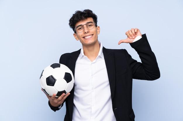 Argentyński trener piłki nożnej ponad izolowaną niebieską ścianą dumny i zadowolony