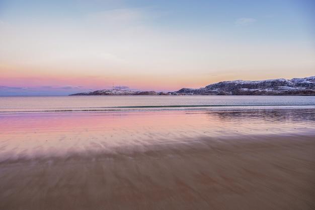 Arktyczna plaża w teriberce. wspaniały arktyczny krajobraz zachodu słońca nad morzem barentsa.