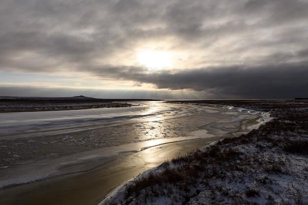 Arktyczny krajobraz w okresie zimowym. mała rzeka z lodem w tundrze.