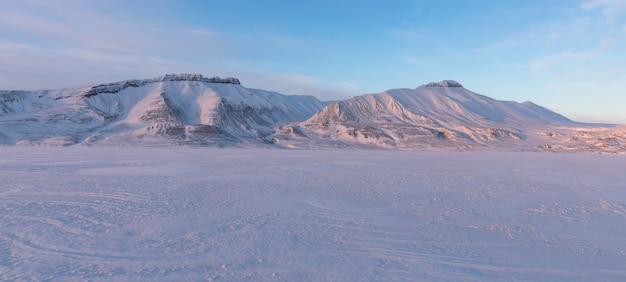 Arktyczny zima krajobraz z zamarzniętym fjord i śniegiem zakrywał góry na svalbard, norwegia