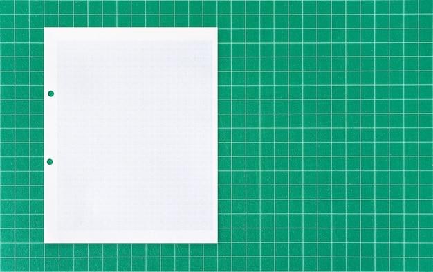 Arkusz białego papieru na zielonej macie.