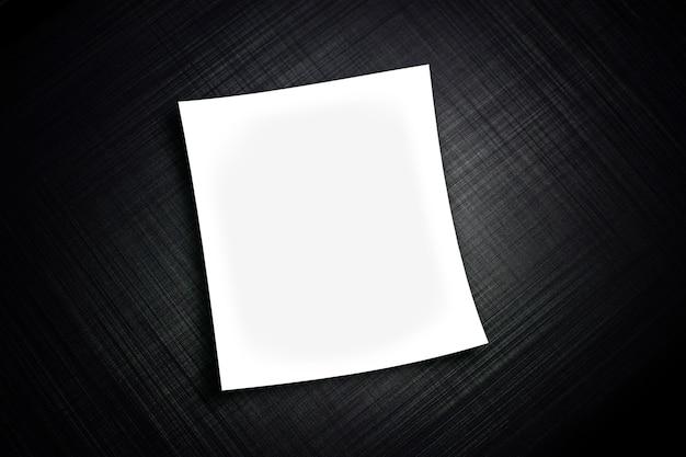 Arkusz białego papieru realistyczny na czarnym tle z teksturą metalu w paski
