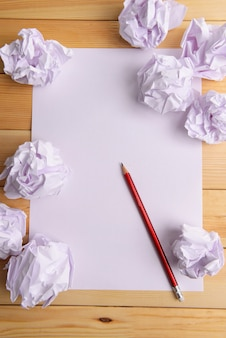 Arkusz białego papieru z pomiętym papierem i ołówkiem na stole z bliska