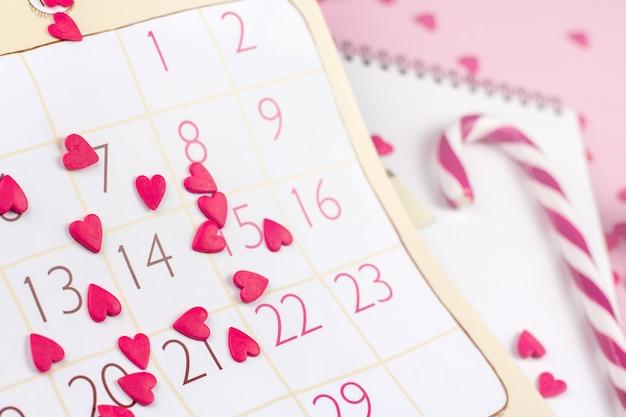 Arkusz kalendarza z datą walentynkową i czerwonymi sercami.