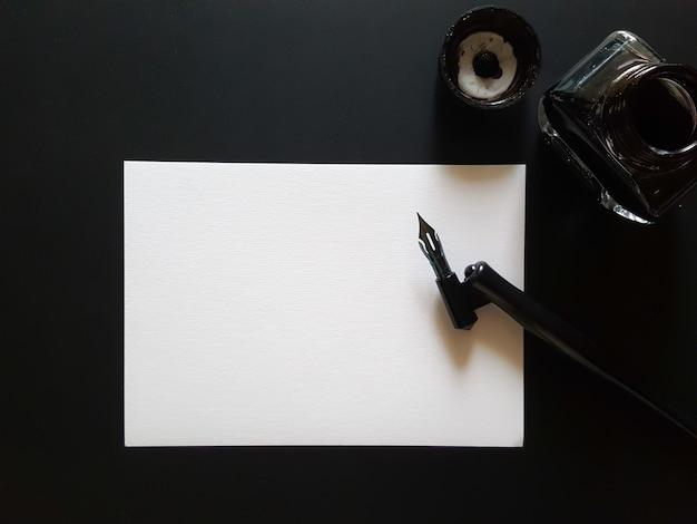 Arkusz papieru, długopis i tusz czarny na czarnym biurku.