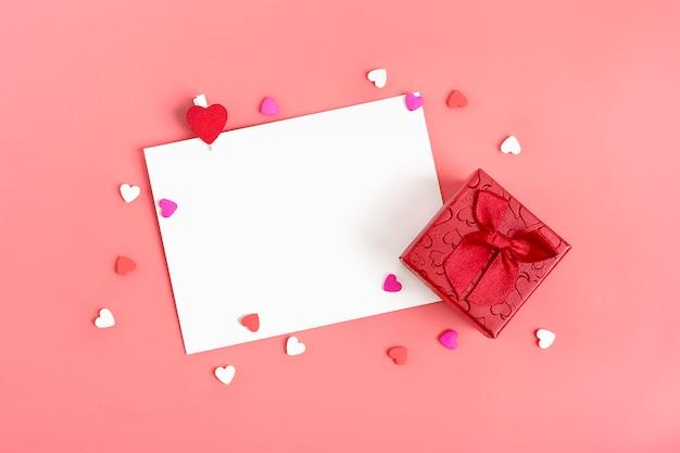 Arkusz papieru do wiadomości, czerwona koperta, pudełko, cukierki w kształcie serca. szczęśliwych walentynek