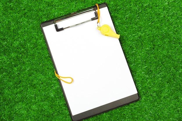 Arkusz papieru i sprzęt sportowy na trawie z bliska