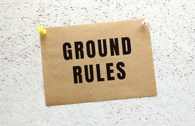 Arkusz papieru rzemieślniczego z napisem ground rules przyczepiony do białej, teksturowanej ściany za pomocą przycisku. przypomnienie o biurze.