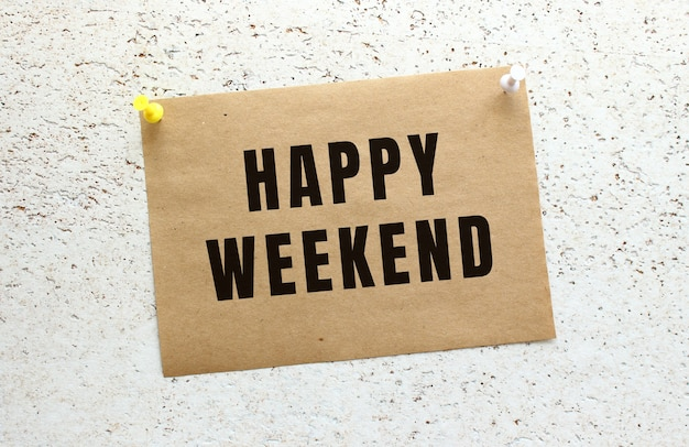 Arkusz papieru rzemieślniczego z napisem happy weekend przyczepiony do białej, teksturowanej ściany za pomocą przycisku. przypomnienie o biurze.