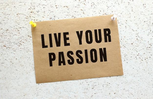 Arkusz papieru rzemieślniczego z napisem live your passion przyczepiony do białej, teksturowanej ściany za pomocą przycisku. przypomnienie o biurze. pomysł na biznes.