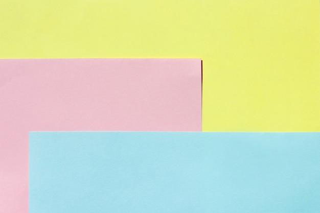 Arkusz papieru w kolorze żółtym, różowym i niebieskim. wielobarwne jasne tło.