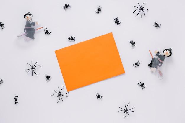 Arkusz papieru z ozdobnymi pająkami i czarownicami wokół