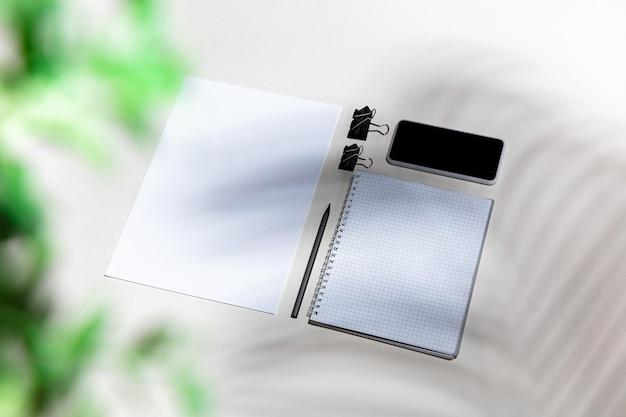 Arkusze, gadżety i narzędzia pracy na białym stole w pomieszczeniu. kreatywne, przytulne miejsce pracy w domowym biurze, inspirująca makieta z cieniami roślin na powierzchni. koncepcja zdalnego biura, freelance, atmosfera.