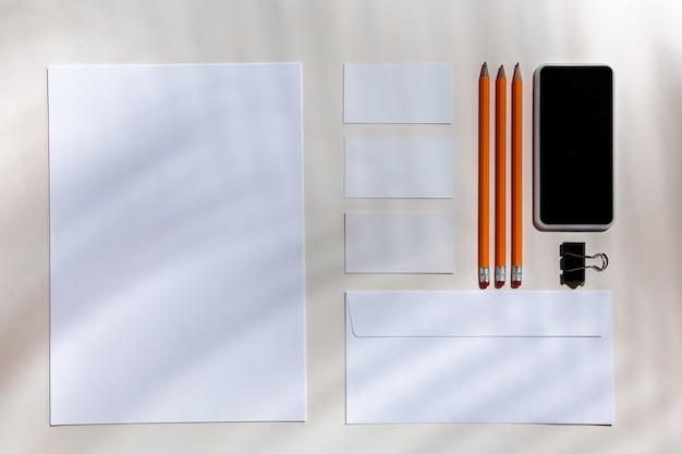 Arkusze, gadżety i narzędzia pracy na białym stole w pomieszczeniu.