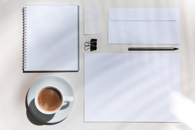 Arkusze, kawa, narzędzia pracy na białym stole w pomieszczeniu. kreatywne, przytulne miejsce pracy w domowym biurze, inspirująca makieta z cieniami roślin na powierzchni. koncepcja zdalnego biura, freelance, atmosfera.