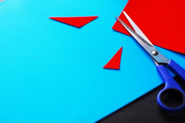 Arkusze kolorowego papieru, opalizująca paleta kolorowego papieru, kolory tęczy. widok z góry na stół z kolorowym papierem i nożyczkami.