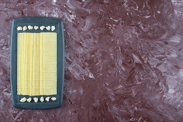 Arkusze lasagne i majonez na drewnianej tacy, na marmurowym stole.