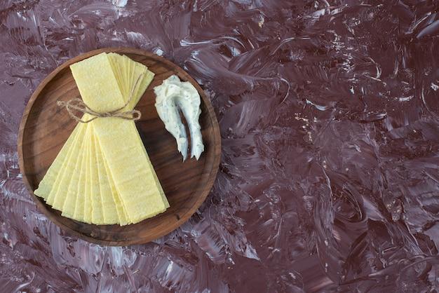 Arkusze lasagne z jogurtem na drewnianym talerzu, na marmurowym stole.