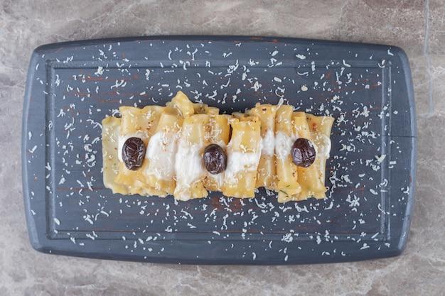 Arkusze lasagne z pieczonym pomidorem na drewnianej tacy, na marmurze.
