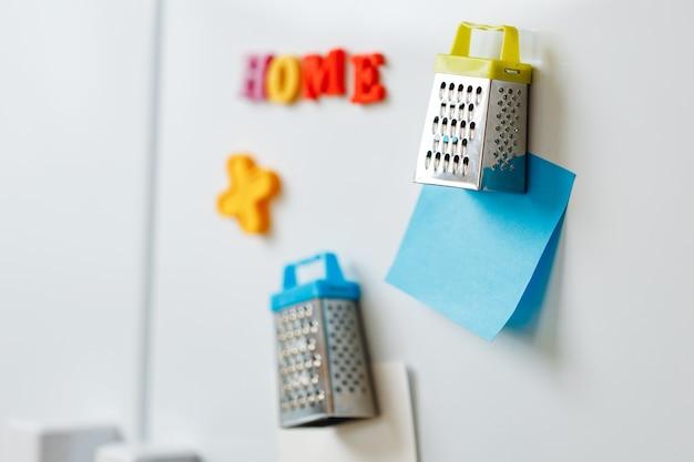 Arkusze papieru i magnesy na drzwiach lodówki w kuchni