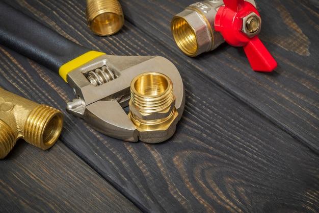 Armatura mosiężna i zbliżenie klucza nastawnego na czarnych drewnianych deskach podczas naprawy lub wymiany części zamiennych