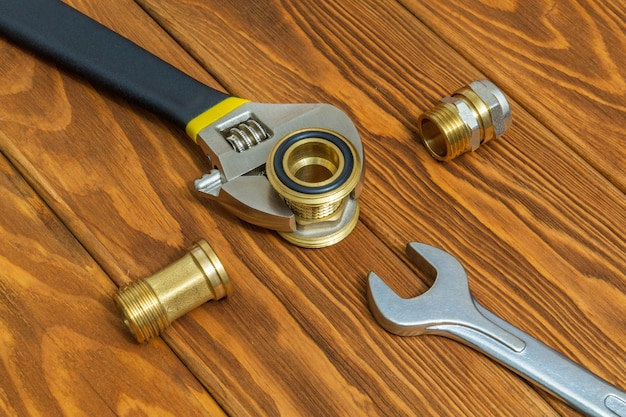 Armatura z mosiądzu i zbliżenie klucza nastawnego na starych drewnianych deskach podczas naprawy lub wymiany części zamiennych