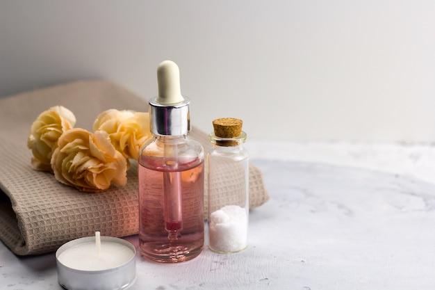 Aromat oleju soli morskiej butelki świeżych kwiatów na stole marmur ręcznik spa welness koncepcja kopia przestrzeń