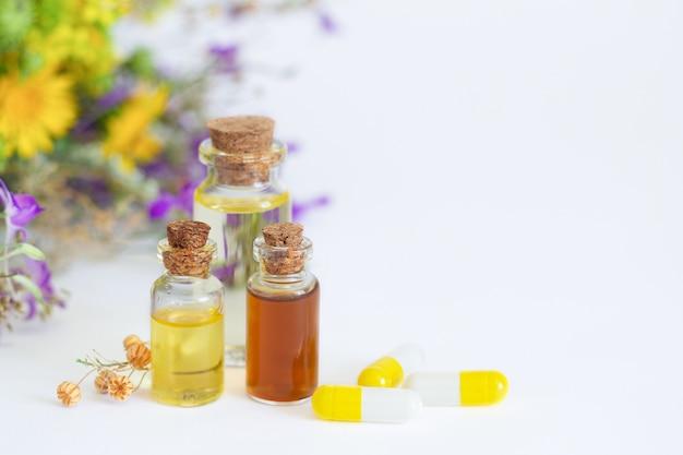 Aromaterapeutyczne olejki do masażu. butelki z olejkami eterycznymi obok pachnących zdrowych kwiatów i naturalnych kapsułek