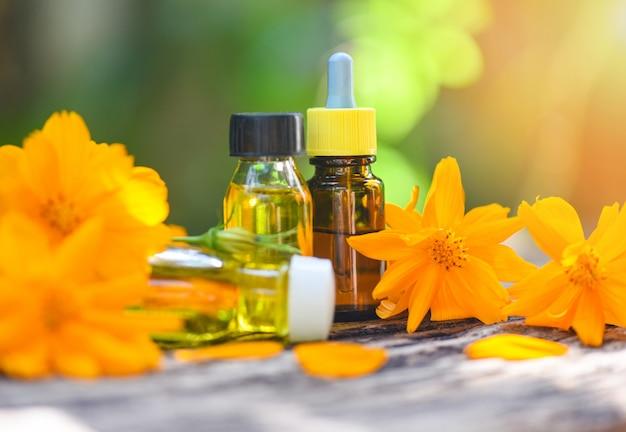 Aromaterapia aromatyczne butelki ziołowych olejków z żółtymi kwiatami na zielonej zieleni olejki eteryczne naturalne do pielęgnacji twarzy i ciała na drewnianym stole i ekologicznym minimalistycznym stylu życia
