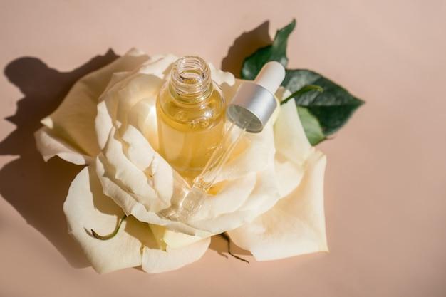 Aromaterapia. biały kwiat i płatki, olejek różany w szklanej butelce. . zdjęcie wysokiej jakości