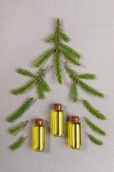 Aromaterapia i kreatywny układ spa z zielonymi gałązkami świerkowymi i małymi szklanymi butelkami aromatycznego olejku z jodły iglastej spa ułożonej jako choinka na szarym tle z teksturą. widok z góry.