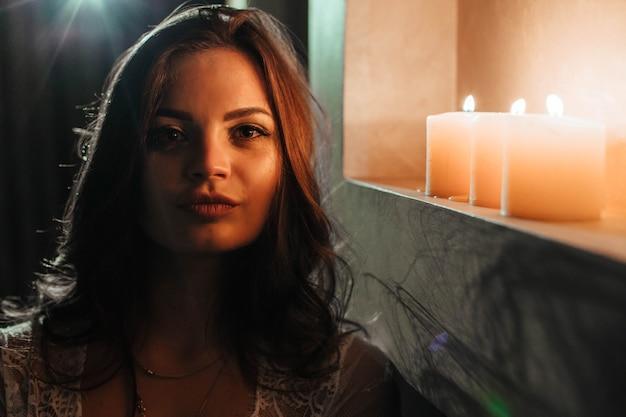 Aromaterapia seksowna brunetka w bieliźnie gasi świece przed snem romantyczne ustawienie