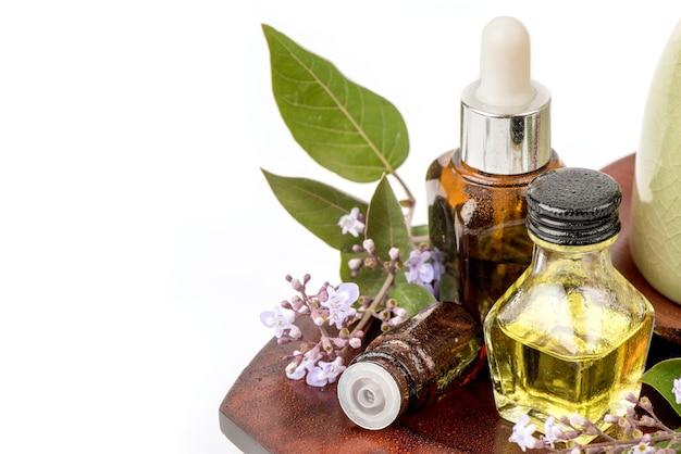 Aromaterapia z kwiatów vitex trifolia purpurea, zielonych liści i olejku eterycznego na białym tle.