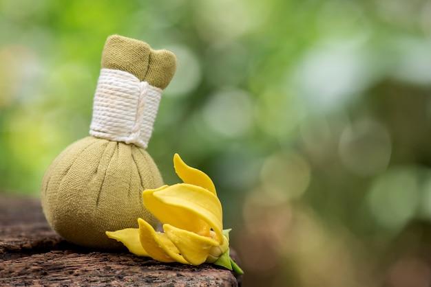 Aromaterapia z pnącym kwiatem ylang-ylang i perfumami w kompresie ziołowym na zielonych liściach bokeh naturalny.